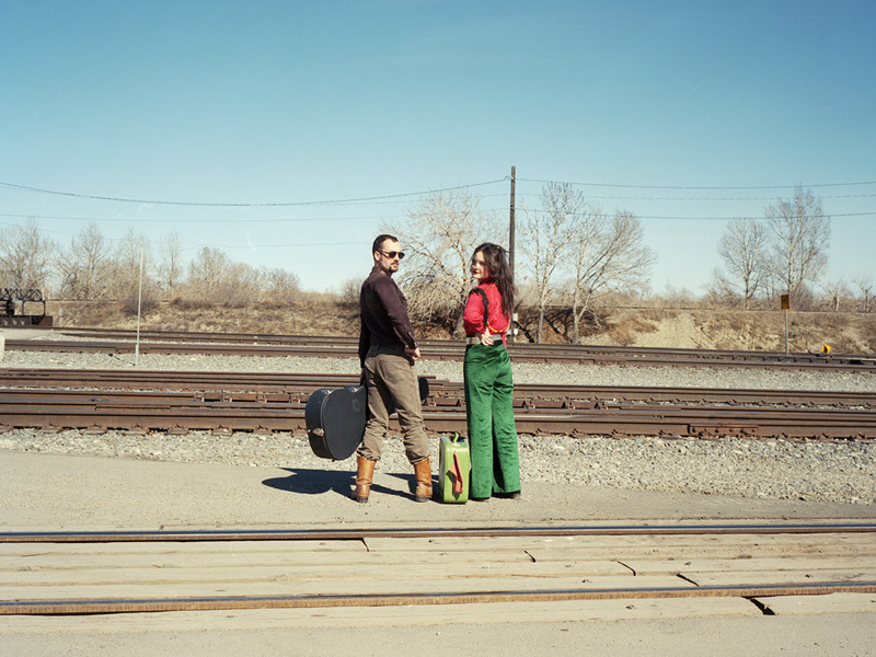 Two people stand in front of railway tracks, one with a guitar case and one with a suit case.