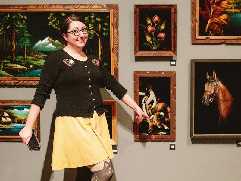 Amy Jo Espetveidt at Glenbow pointing at a velvet painting