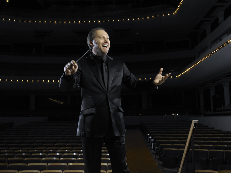 A conductor emphatically stands in front of an empty theatre