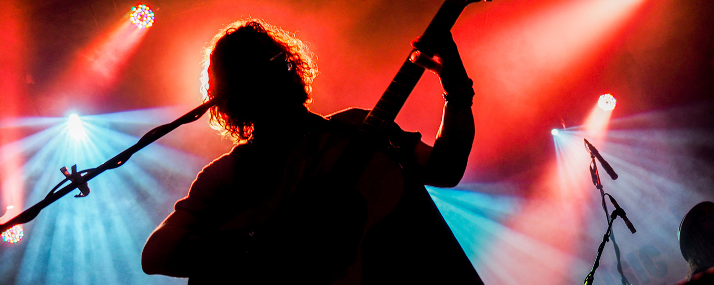 A man plays a guitar with red and blue lights behind him