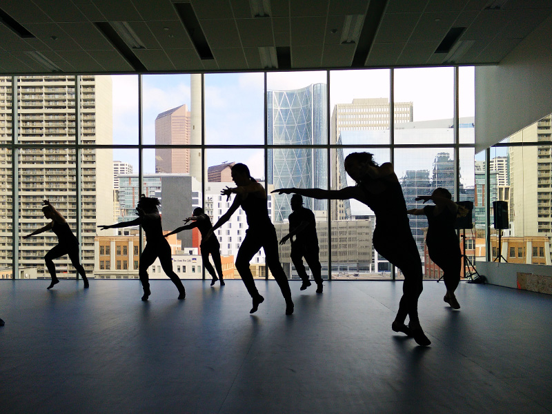 Dancers silhouetted in a studio overlooking downtown Calgary