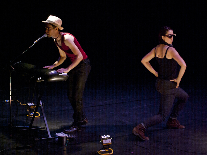 A man plays a keyboard while a woman in dark glasses strikes a pose