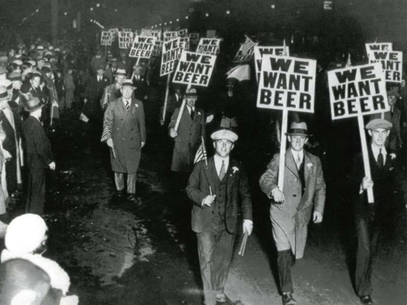 """A historical photo of a group holding """"We Want Beer"""" placards"""