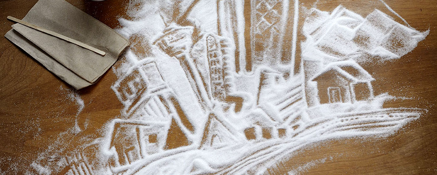 The Calgary skyline drawn in sugar on a table with coffee cups