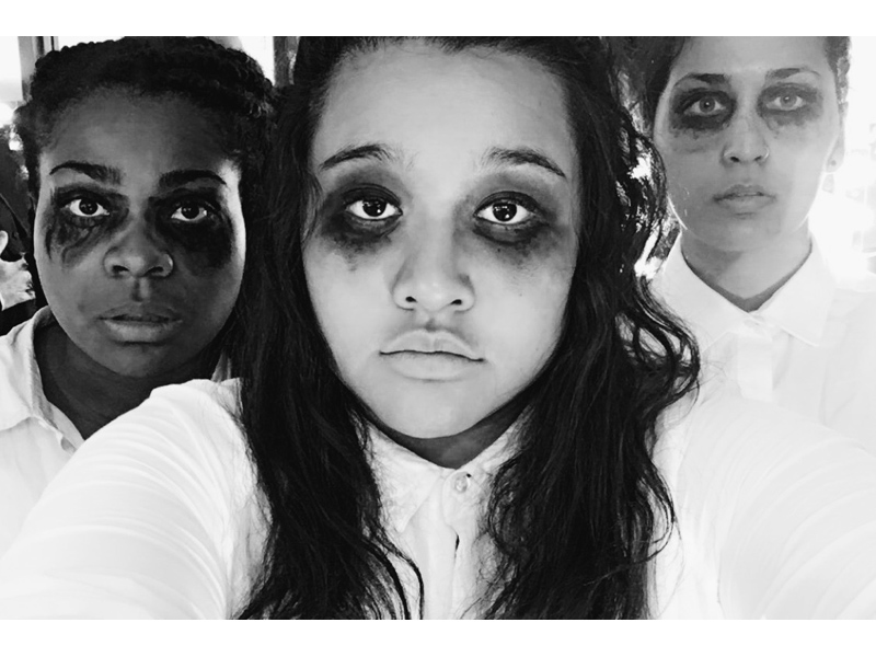 Three performers with blacked out eye makeup stare into the camera