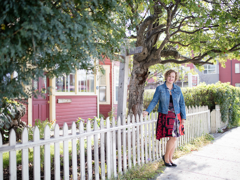 A woman stands next to a white picket fence