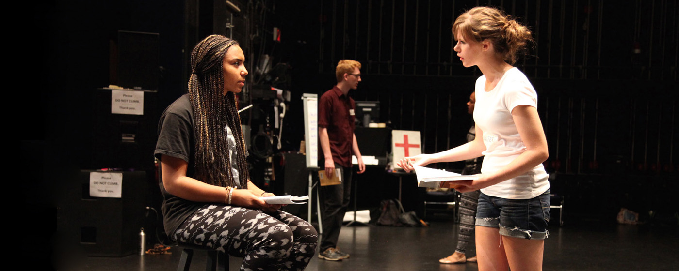 Two girls rehearse a theatre scene while holding scripts
