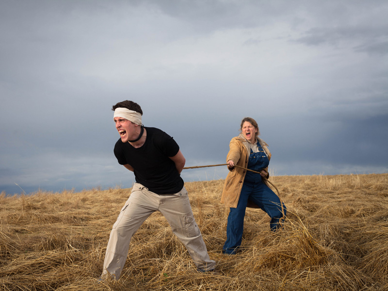 A woman pulls a man with his arms tied behind his back using a rope