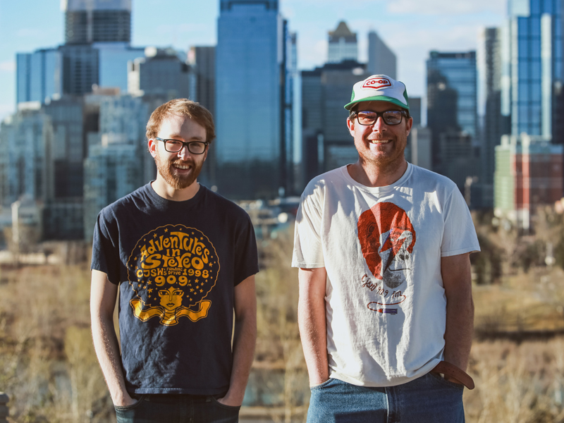 From We Make Radio, longtime volunteers, Cailean David and Greg Chernoff show off their favourite Funding Drive t-shirts from years past | Photo: Courtesy of CJSW
