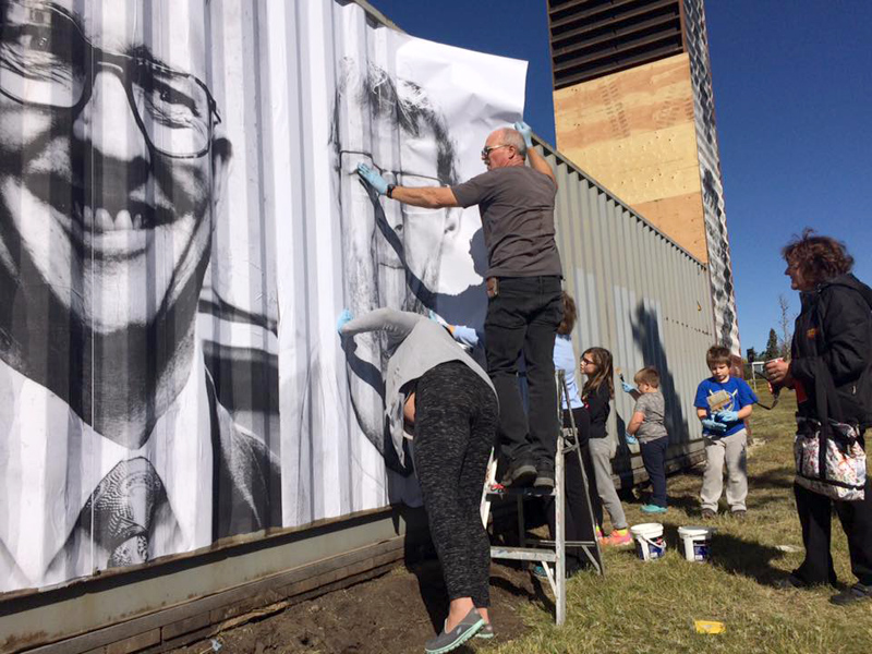Community members get a bit mucky and help paste up portraits for Eyes on the Ave containR Installation | Photo: Courtesy of IAACC