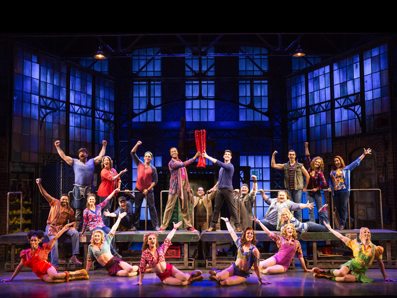 A large cast strikes a pose on stage with a pair of bright red boots