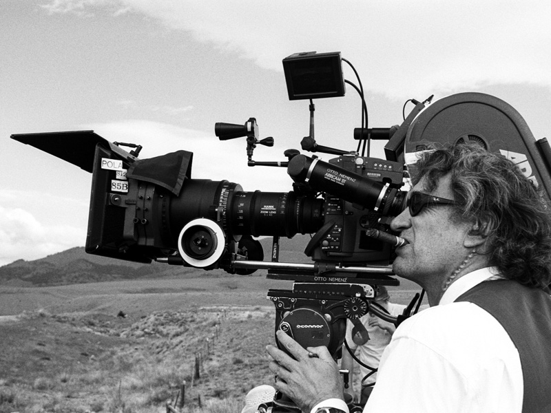 A black and white image of a man wearing sunglasses behind a large movie camera.