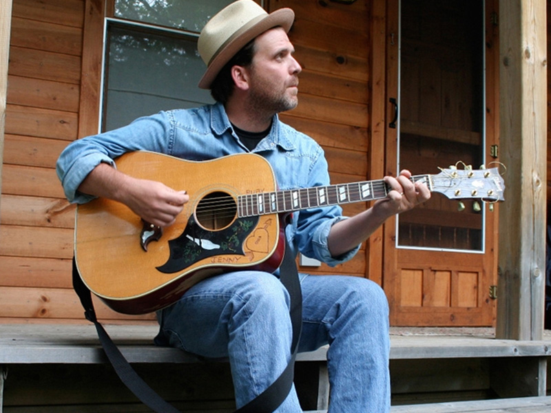 A man plays an acoustic guitar on a front porch.
