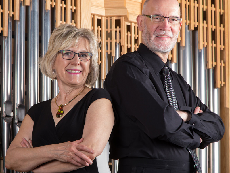 A man and a woman with their arms crossed stand in front of an organ
