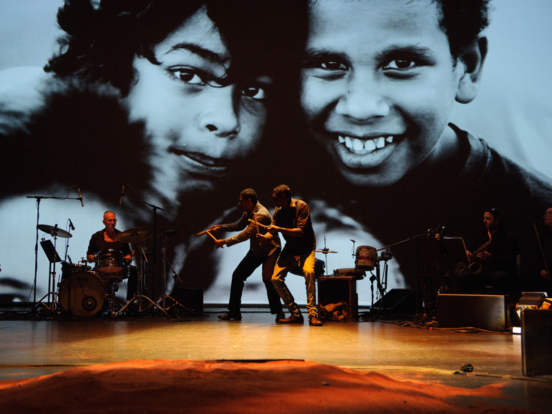 Musicians play on stage in front of an image of two children
