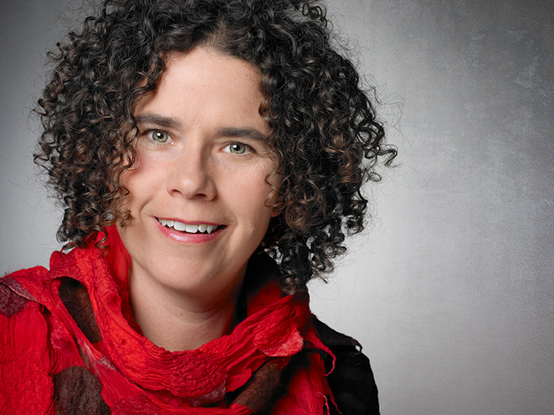 Portrait of a woman with curly hair and a red scarf.