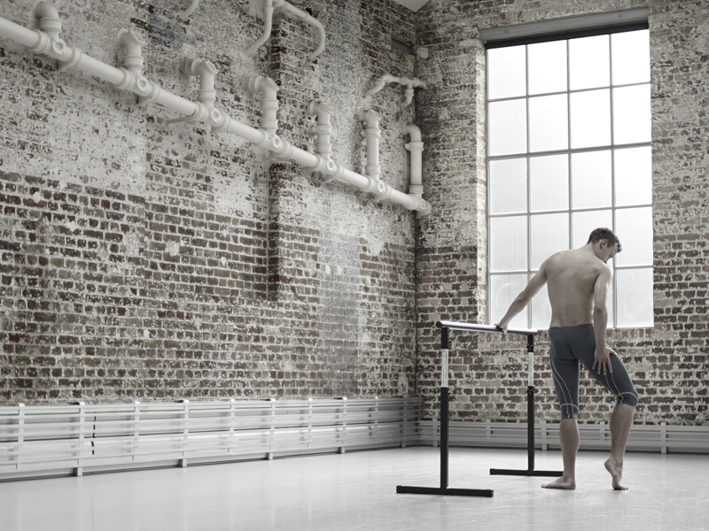 A male ballet dancer against a brick studio wall