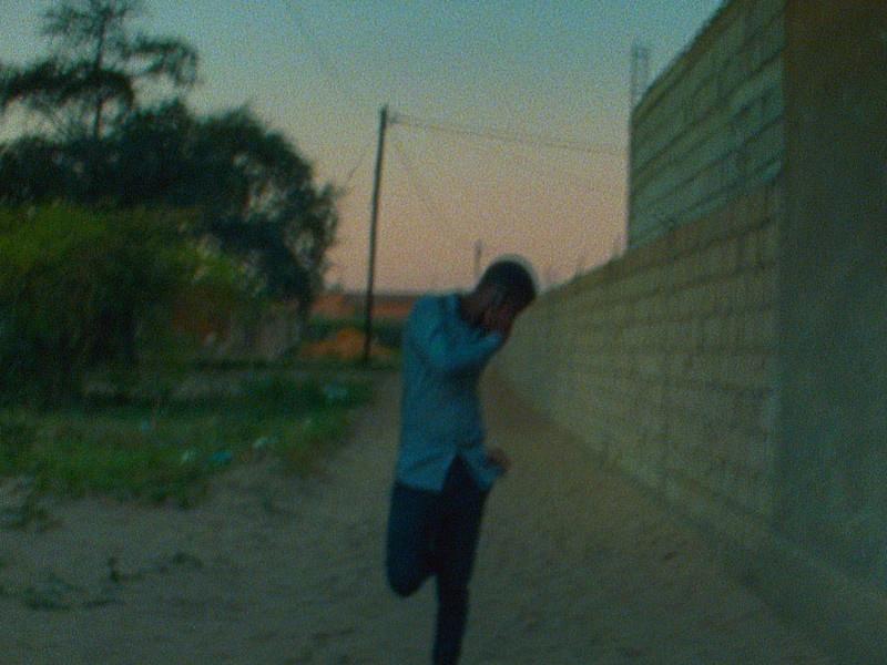 A man runs through an alley in a grainy film still