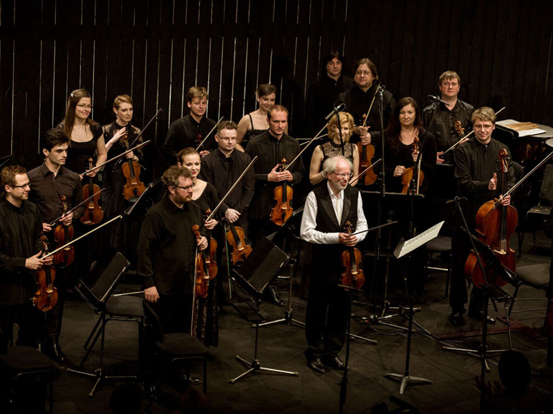 A man with a violin stands surrounded by an orchestra