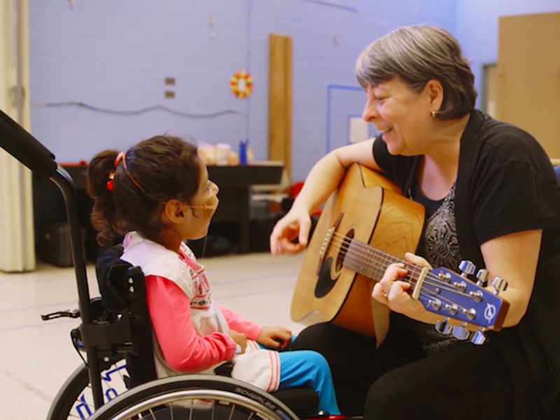 A woman plays guitar to a girl in a wheelchair