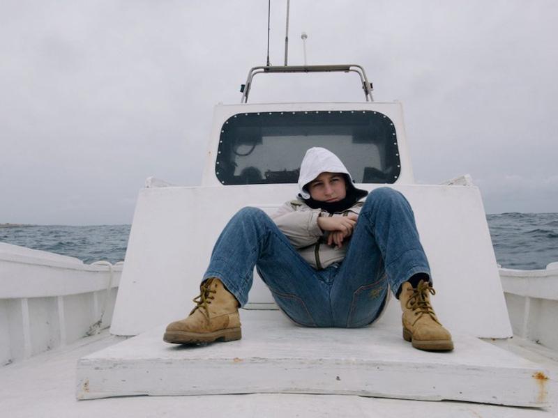 A man sits huddled on an open ship deck