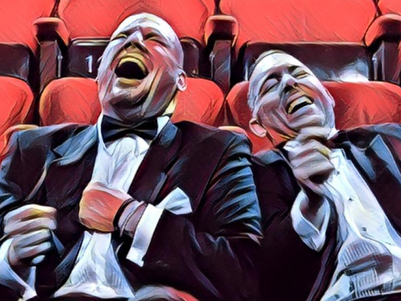 Painting of two men laughing in the seats of the Loose Moose Theatre
