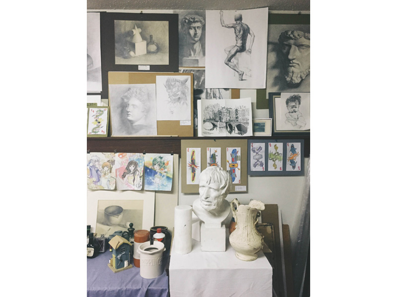 A photo of a studio with sketches and paintings pinned to the wall