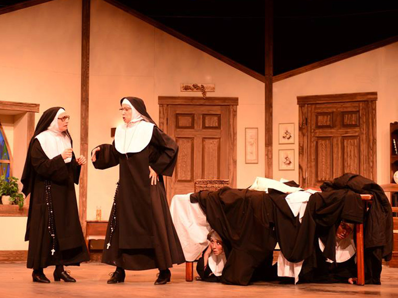 Two nuns talk while two hide under a table, eavesdropping