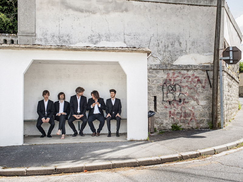 Five musicians sit in a bus stop next to a brick wall