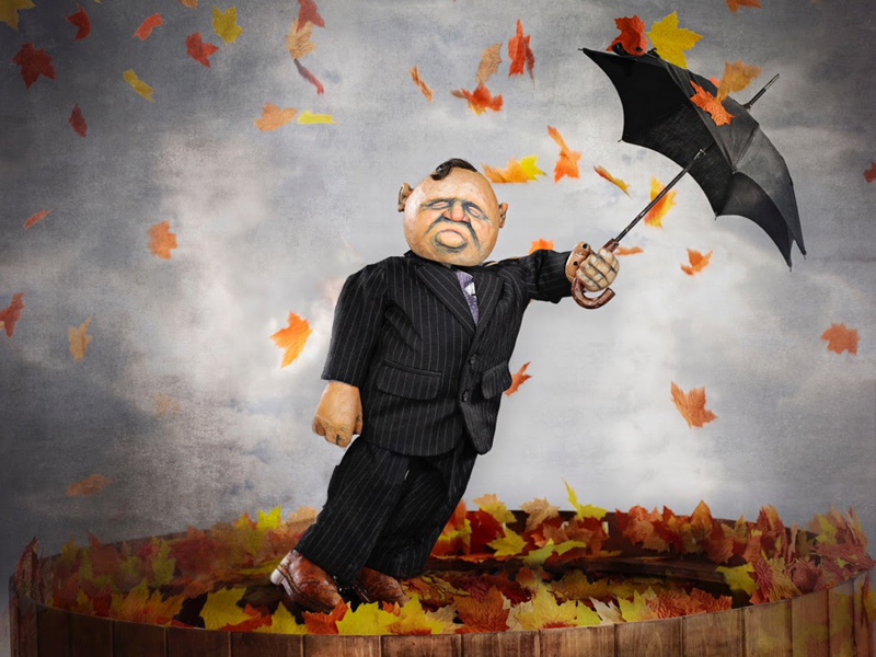 A puppet with an umbrella and blowing leaves