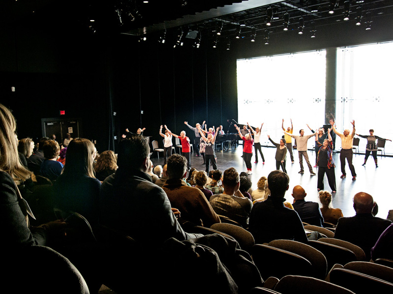 Dancers on a stage with an audience watching