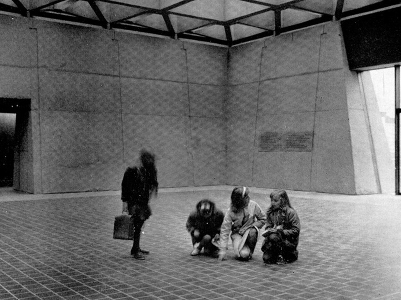 Black and white photo of four people in a large room