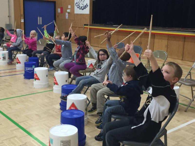 A photo of children drumming on buckets