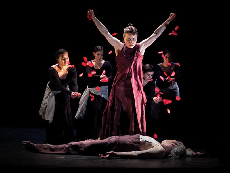 A flamenco dancer throws rose petals over a body