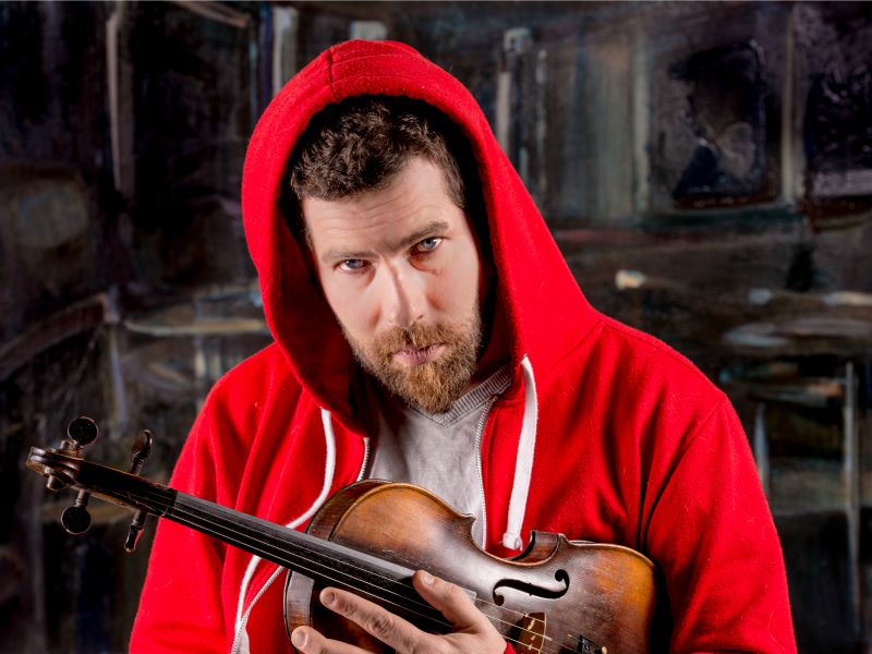A photo of Ashley Macisaac and his fiddle