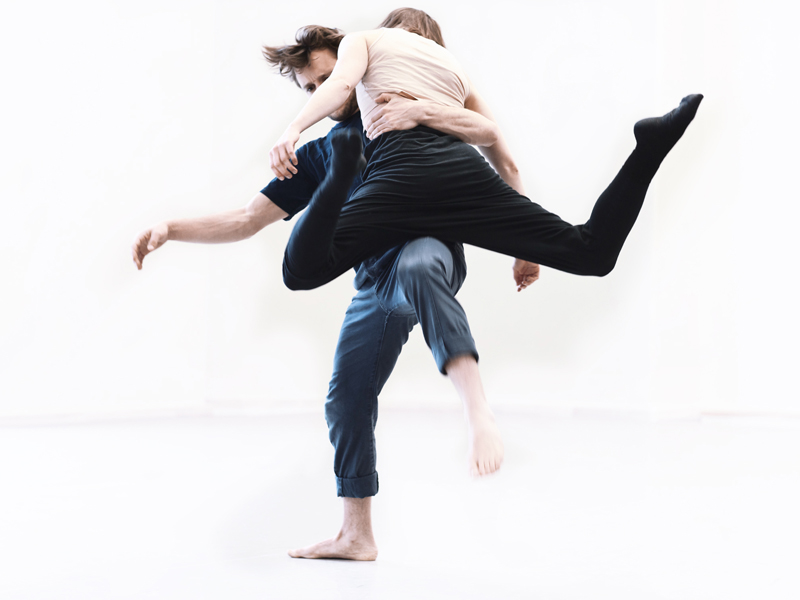 Two dancers embrace on a white stage