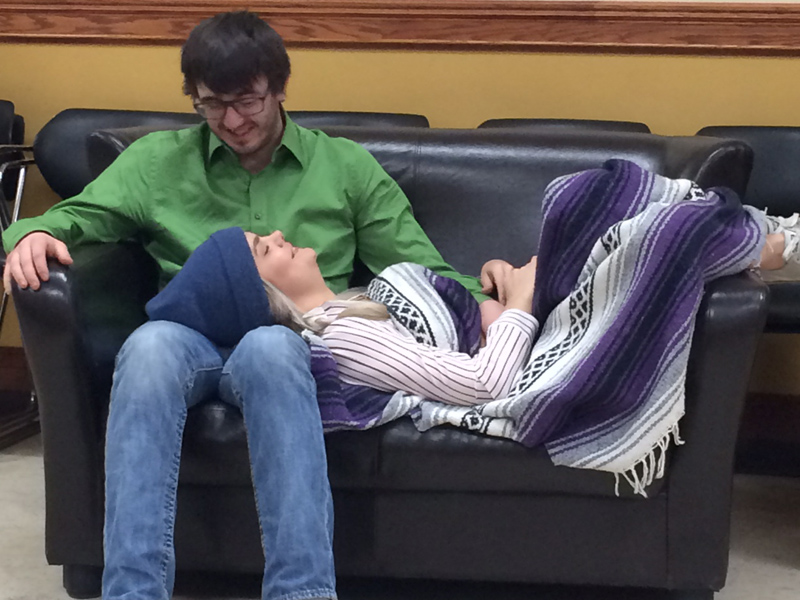 A man sits on a couch as a woman lays across his lap wrapped in a blanket
