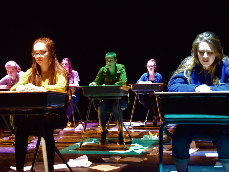 Students on stage sitting at desks