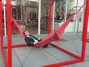 A photo of Gregory Burbidge wearing a suit in a hammock