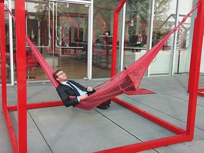 A photo of Gregory Burbidge wearing a suit in a hammock