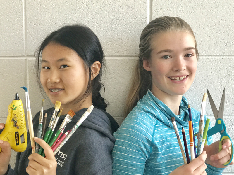Rona Kong and CJ Sauve hold up art supplies