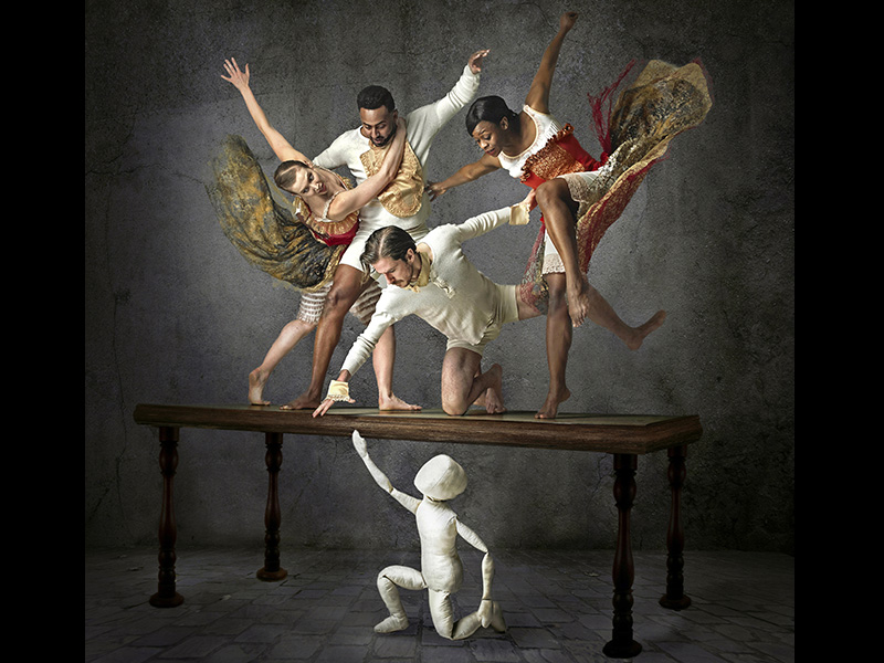 Dancers pose on a table above a blank white puppet