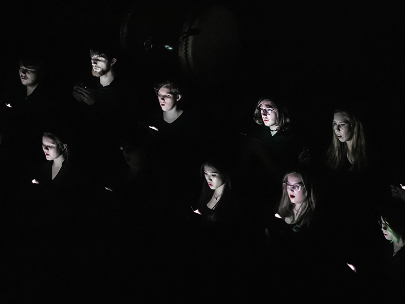 Photo of Mount Royal Artio singing with lights illuminating their faces