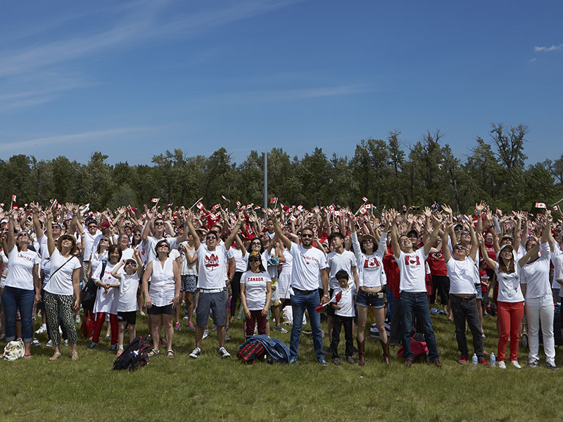A group photo of hundreds wearing Canada t-shirts and waving flags