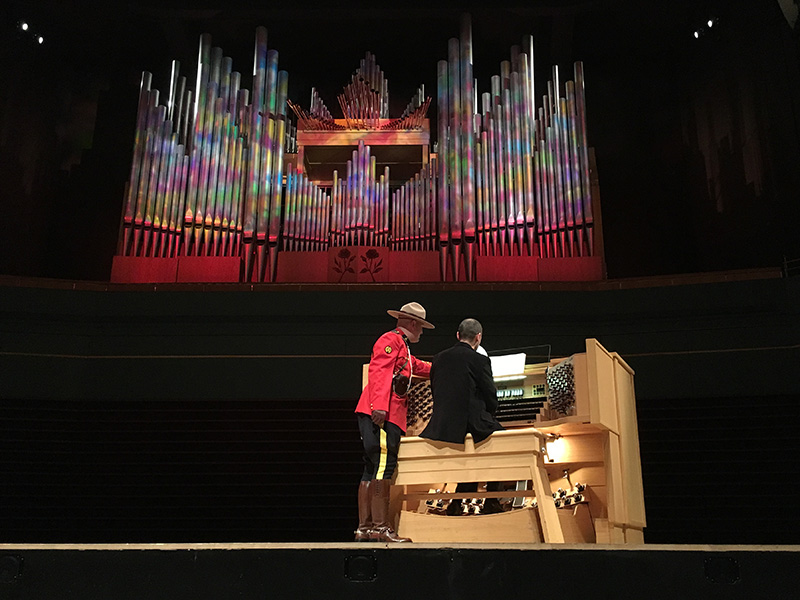 Photo of an organ lit up and a Mountie next to a performer