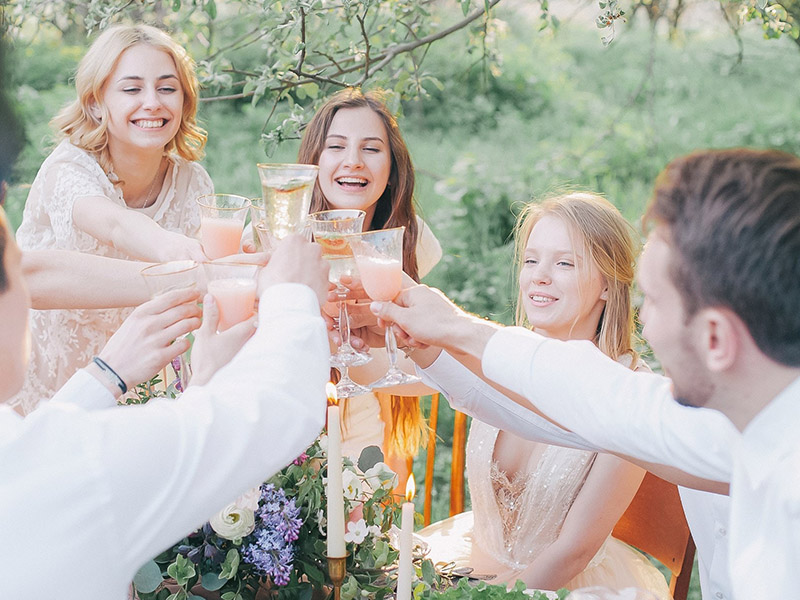 A group of people toast champagne flutes in a beautiful garden