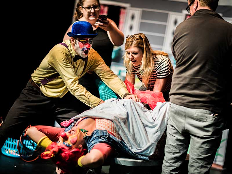 Three people help two clowns, one of whom appears to be giving birth