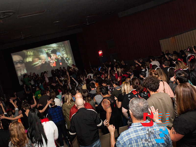 Audience members stand up and dance at the Calgary Underground Film Festival, Calgary Queer Arts Society, and Hole in the Wall Studios screening
