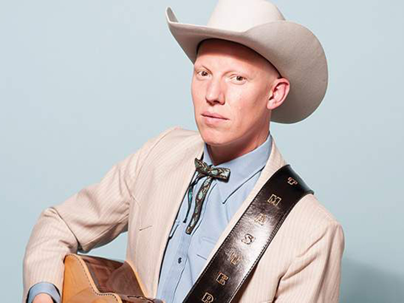 Photo of Matt Masters in western wear holding a guitar