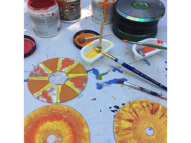 A photo of orange and yellow paintings on old CDs
